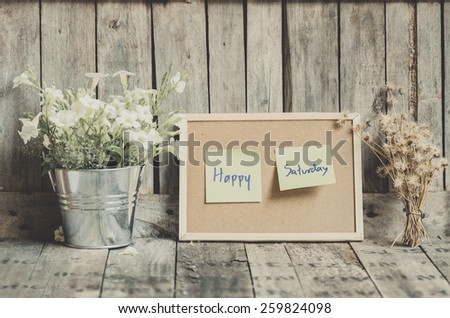 Vintage style effect Happy Saturday message on corkboard with flowers  by wooden background