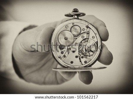 Vintage style image. Hand holding antique pocket watch show the clockwork mechanism.