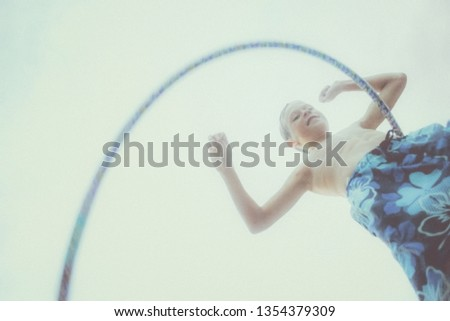Vintage style image of a smiling boy dancing with a hoop, retro noise added