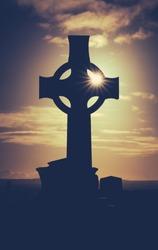Vintage Style Image Of Sun Glinting Through A Celtic Cross Gravestone