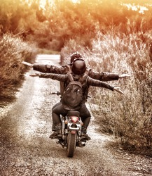 Vintage style image, rear view of two happy bikers riding on the road with raised up hands, active family enjoying journey on luxury extreme transport, freedom concept