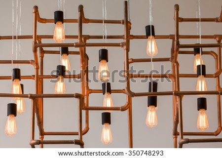 Vintage style light bulbs hang and decorated with alloy pipes in a living room #350748293