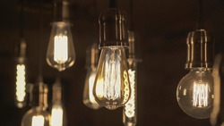 Vintage style light bulbs hanging from the ceiling. Decorative lights at home. Old Edison bulb.