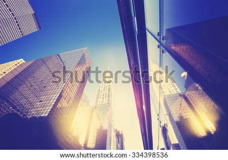 Vintage style Manhattan skyscrapers at sunset reflected in windows, NYC, USA. #334398536