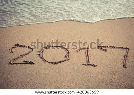 Vintage style 2017 message written in the sand at the beach background #420065659