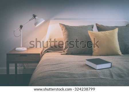 vintage style photo of cozy bedroom interior with book and reading lamp on bedside table
