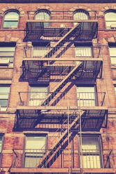 Vintage style photo of New York building with fire escape ladders, USA.