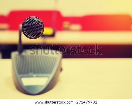 Vintage style photo of the microphone in conference  room or symposium event with de focused meeting room in background. Extremely shallow dof. Filtered process.