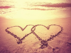 Vintage style photo of two hearts shape draw on the sand of a beach in morning time. Concept for love or wedding ceremony. Filtered process.