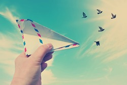 Vintage style photo with hand throwing a paper plane (made of Post envelope) and the flying pigeons against beautiful blue sunny sky