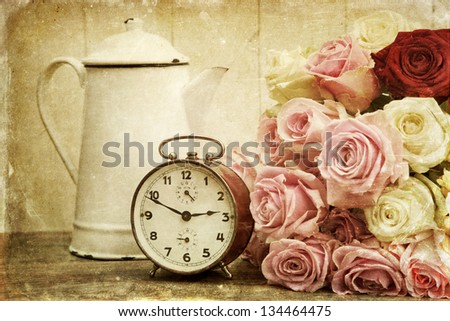 vintage style picture of an arrangement with a bouquet of roses, an old alarm clock and an old coffee can