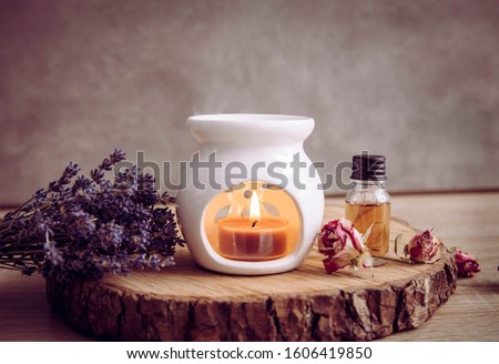 Photo of  Vintage style picture of white ceramic candle aroma oil lamp with essential oil bottle and dry flower petals on natural pine wood disc, dry background with copy space.