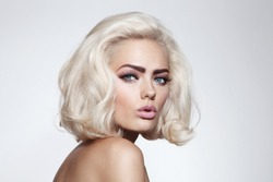 Vintage style portrait of young beautiful blonde girl with fancy makeup