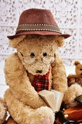 vintage style teddy bear iwearing a hat and glasses reading a book