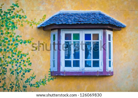 Vintage style window on yellow wall with green leaves painted