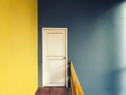 Vintage style with grain filter of empty hallway to small room of white door with yellow and green blue wall and wooden floor lighted with sun light from window on right side, warm colour tone
