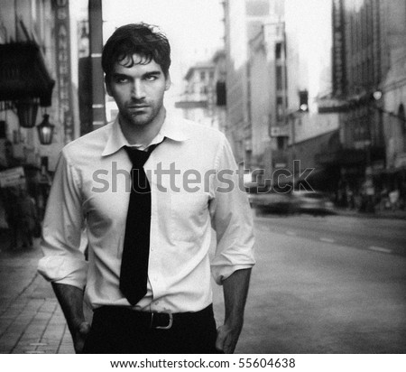 Vintage stylized black and white photo of young male model against city street (Photo has an intentional film grain)