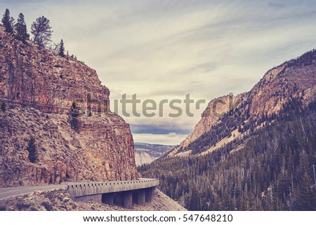 Vintage stylized photo of a road in Yellowstone National Park, Wyoming, USA.