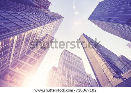 Vintage stylized picture of Manhattan skyscrapers at sunset, looking up perspective, New York City, USA.  #710069182