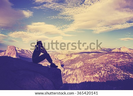 Vintage stylized silhouette of a woman watching mountain view at sunset, Yosemite National Park, USA.