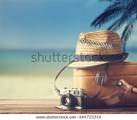 Vintage suitcase, hipster hat, photo camera and passport on wooden deck. Tropical sea, beach and palm three in background. Summer holiday traveling design concept. - Shutterstock ID 644723314