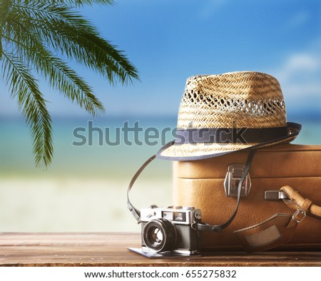 Vintage suitcase, hipster hat, photo camera and passport on wooden deck. Tropical sea, beach and palm three in background. Summer holiday traveling design concept. - Shutterstock ID 655275832