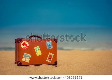 vintage suitcase on sandy beach ...