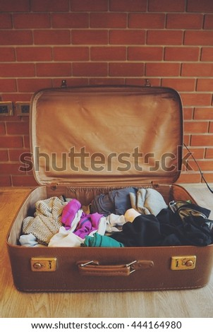 Vintage suitcase open on a wood floor in vintage color #444164980