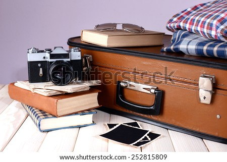 Vintage suitcase with clothes and books on table on dark colorful background