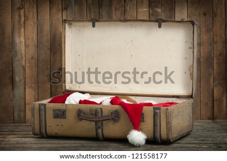 vintage suitcase with santa clothes, on an old wooden floor
