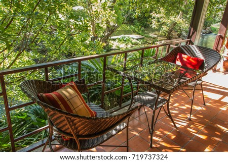 Vintage table and chairs for indoor terrace lounge with garden background in morning sunny day, concept of relaxation zone