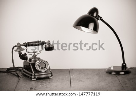 Vintage telephone and old desk lamp on table