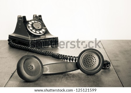 Vintage telephone handset on old table sepia photo