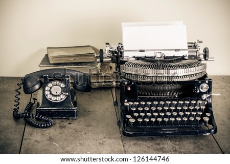 Vintage telephone, old typewriter, books on table desaturated photo