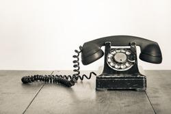 Vintage telephone on old table sepia photo