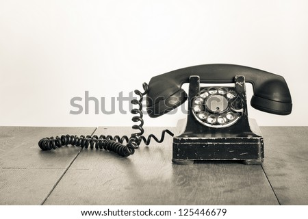 Vintage telephone on old table sepia photo #125446679