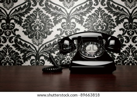Vintage telephone over ornate wallpaper with copy space