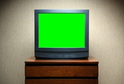 Vintage Television on wooden antique closet, old design in a home.Old black vintage TV with green screen to add new images to the screen.