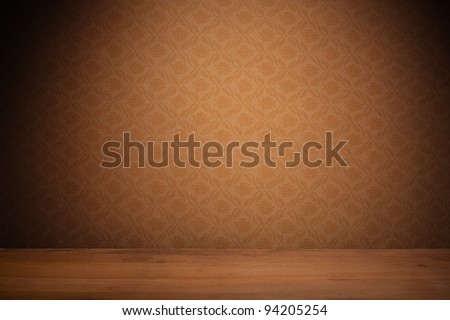 Vintage textured brown wallpaper with heavy vignetting over a wooden floor, empty with copyspace.