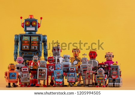 Vintage tin robot toys isolated on a yellow background.