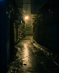 Vintage tone a dark, shadowy and dangerous looking urban back-alley at night time in suburbs Hanoi, Vietnam. Low light reflected on wet pavement from post lamp at the end of long road corner