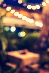 Vintage tone abstract blur image of Restaurant in night time with light bokeh for background usage .