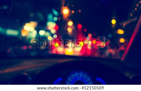 vintage tone blur image of people driving car on night time,during raining  for background usage.(take photo from inside)