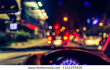 vintage tone blur image of people driving car on night time for background usage. (take photo from inside)