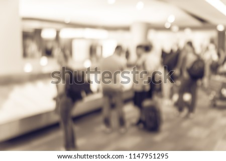 Vintage tone blurred motion diverse group of passengers waiting for their luggage at baggage claim area of San Francisco International Airport. Defocused background suitcase on conveyor belt