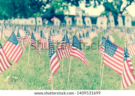 Vintage tone close-up lawn American flag with row of people from Memorial Day March event in Dallas, Texas, USA. Blurry crowded family members carry fallen heroes banners pictures placards in parade