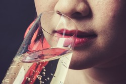Vintage tone Close up thin focus on red lip Asian young woman drinking champagne