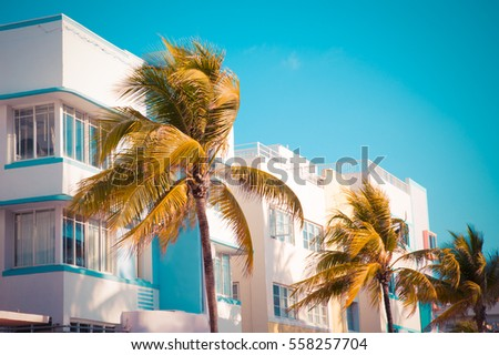 Vintage tone image of palm trees and typical retro art deco style buildings seen from South Beach Miami Florida  #558257704