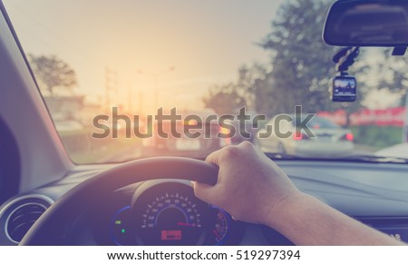 vintage tone image of people driving car on day time for background usage.(take photo from inside focus on driver hand)