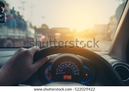 vintage tone image of people driving car on day time for background usage.(take photo from inside focus on driver hand).